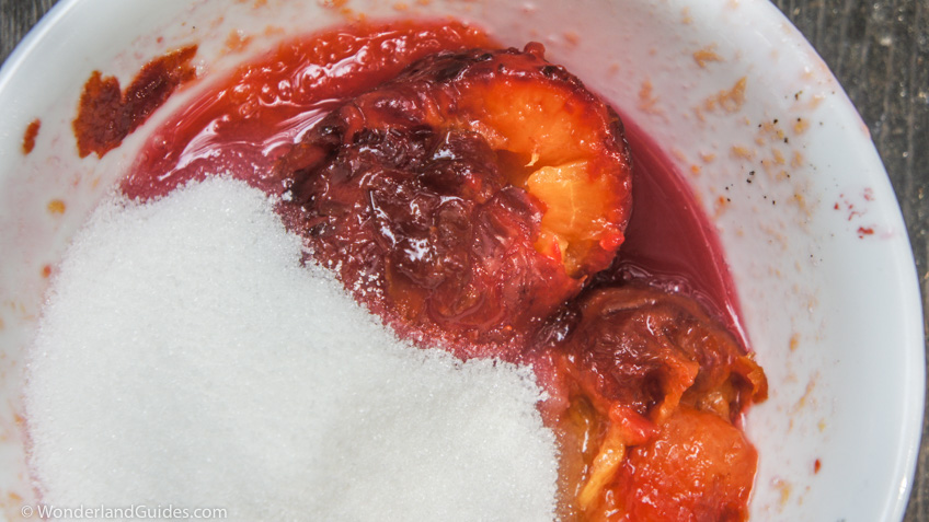 Adding sugar to mashed plums.