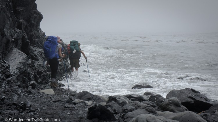 Hikers struggle around an outcrop on the Lost Coast Trail